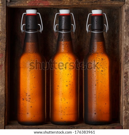 Beer bottles with vintage swing tops in old wooden crate still life - stock photo