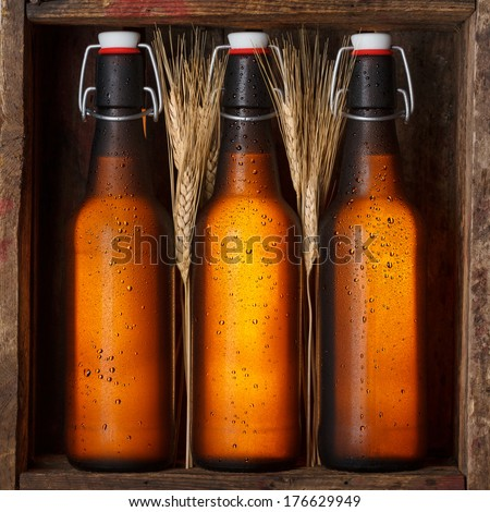 Beer bottles with wheat stems in old wooden crate still life - stock photo