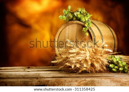 Beer, brewery background. Fresh green hop and wheat with wooden barrel on vintage table. Ingredients for brewing. Retro style. Beer brewing traditions. Copy space for your text - stock photo