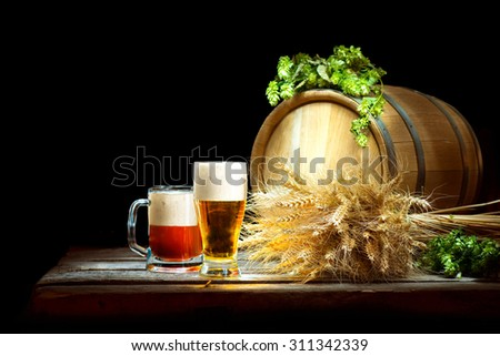 Beer concept. Wooden Barrel and two mugs with beer and fresh hop with ears of wheat isolated on black background. Beer production ingredients. Unbottled beer over dark. Traditions of brewing - stock photo