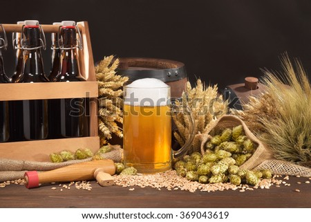 beer crate, beer barrel and beer glass with hops, wheat, grain, barley and malt - stock photo