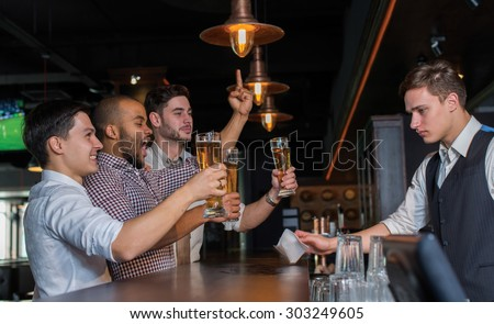 Beer evening in a pub. Male friends are drinking beer in a pub after working day. Beer glasses.  Beer pub concept. Men football and beer