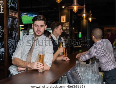 Beer evening in a pub. Portrait of young successful and handsome man drinking beer in a pub with his friends. Beer glasses.  Beer football pub concept.