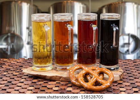 beer flight of four sampling mugs of light and dark craft beer with beer fermenter background - stock photo