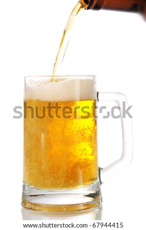 Beer flows from a bottle in a glass, on a white background is isolated.