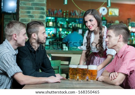 Beer for gentlemen. Beautiful young waitress serving beer while three men sitting at the table in beer pub
