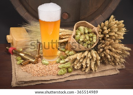 beer glass and beer barrel with hops, wheat, grain, barley and malt