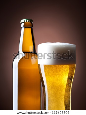 beer glass and bottle on a brown  background