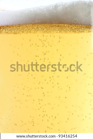 Beer glass close-up shot with bubbles and froth - stock photo