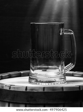 beer glass of beer on a wooden barrel. Black - white.