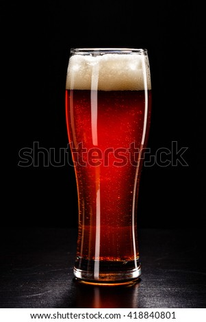 Beer Glass on black. Bar drink. Beer bubbles closeup. DRAFT DARK. Overflow beer glass. Beer beverage. Glass of alcohol. Closeup draft beer glass. Cold Beer. Pint of beer. Good for brewery commercial - stock photo