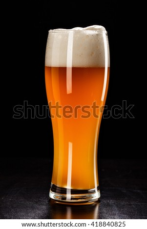 Beer Glass on black. Bar drink. Beer bubbles closeup. DRAFT LIGHT. Overflow beer glass. Beer beverage. Glass of alcohol. Closeup draft beer glass. Cold Beer. Pint of beer. Good for brewery commercial