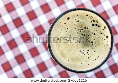 Beer glass on red and white vintage tablecloth background - Vintage style pictures - stock photo