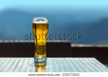 beer glass on the bar table at the open-air cafe in mountains     - stock photo