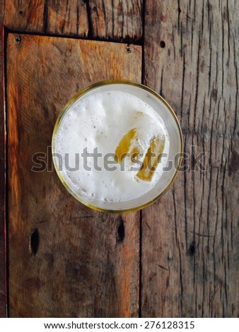 Beer glass on wooden table - stock photo
