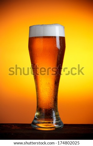 Beer glass on wooden table still life - stock photo