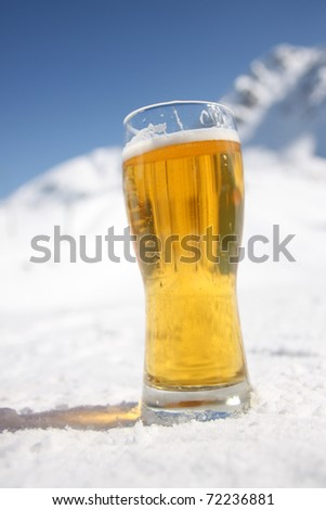 Beer glass over Alps in the snow - stock photo