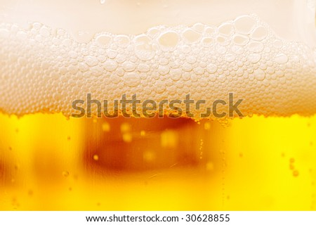 Beer glass surface macro with foam and some bubbles - stock photo