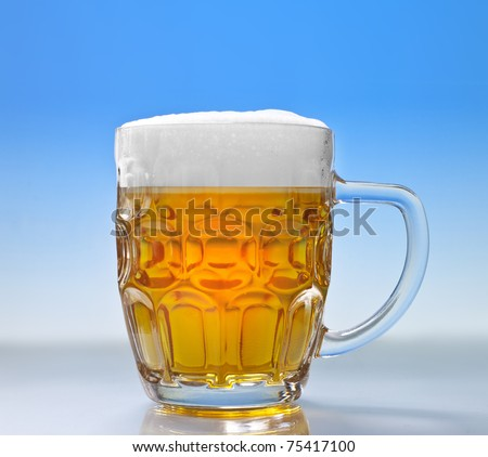 Beer glass with froth over blue background - stock photo