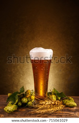 Beer glass with wheat and hops on wooden table