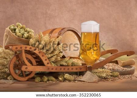 beer glass with wood barrel with wheelbarrow, hops, wheat, grain, barley and malt - stock photo