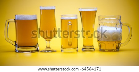 Beer glass with yellow background - stock photo