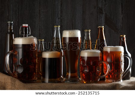 Beer glasses and bottles with lager, dark lager, brown ale, malt and stout beer on table, dark wooden background - stock photo