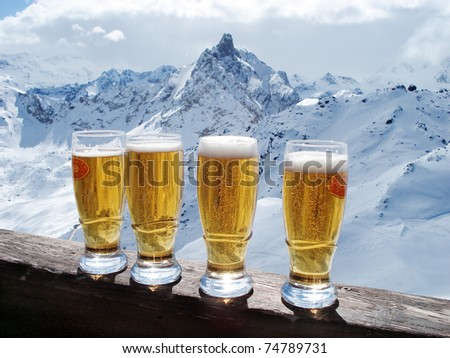 Beer glasses over Alps - stock photo