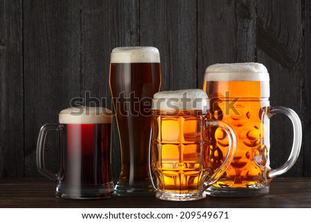 Beer glasses with various beer on table, dark wooden background - stock photo