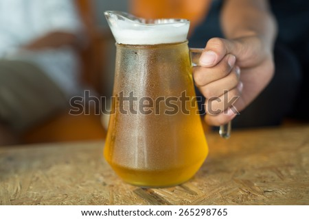 Beer in a glass jar with hand holding - stock photo