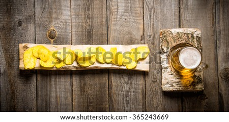 Beer in a glass on a birch stand and chips on a wooden log. On a wooden table. Top view - stock photo