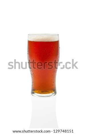 Beer in a pint glass with drop shadow isolated against white background. - stock photo