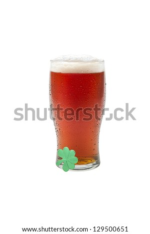 Beer in a pint glass with St Patrick theme, isolated against white background. - stock photo