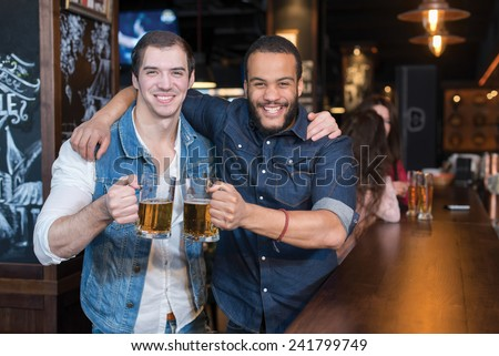 Beer in a pub is fun Portrait of two handsome friends in a pub w - stock photo
