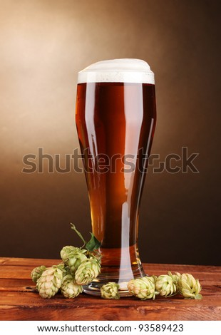 beer in glass and green hop on wooden table on brown background - stock photo