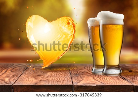 Beer in glass and splash in shape of heart on wooden table with blurred autumn city park on background, natural background with bokeh - stock photo