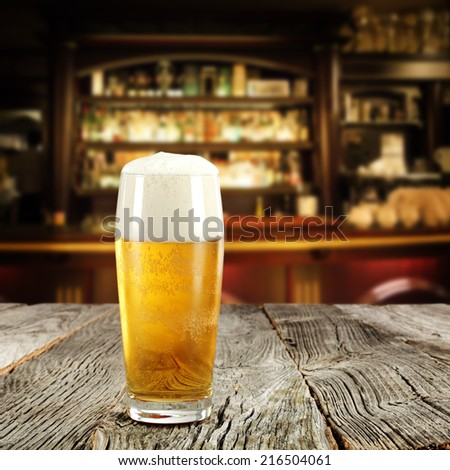 beer in glass and wooden top in bar
