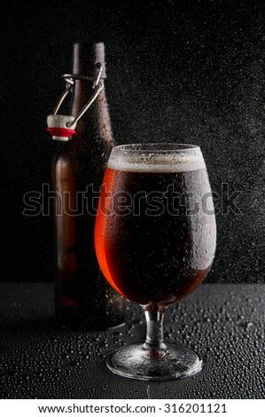 Beer in glass on a black background - stock photo
