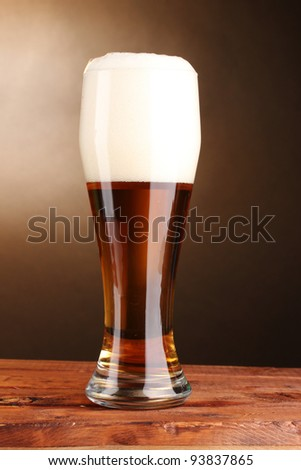 beer in glass on wooden table on brown background