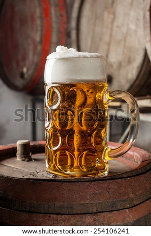 Beer in glass with foam on old wood barrel with other barrels in the background - stock photo