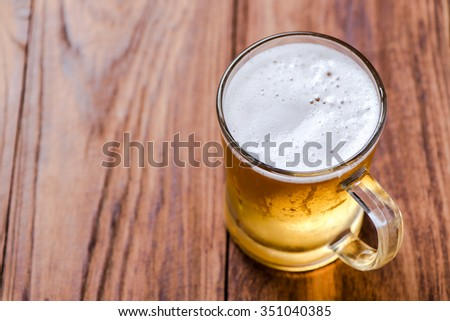 Beer in mug glass on wood table - stock photo