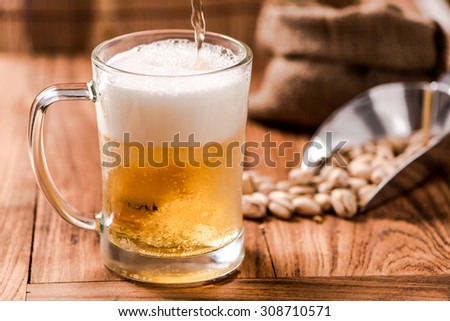 beer in mug glass pouring from top with bean on wood table - stock photo