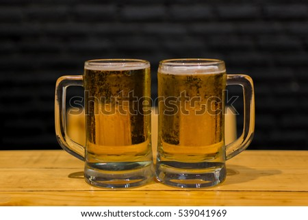 Beer in mug glass with ice and froth on a wood table
