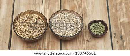 beer ingredients, hops and malt on wooden table top - stock photo