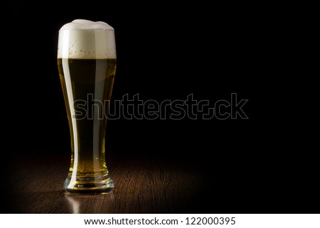 Beer into glass on a black and wooden table