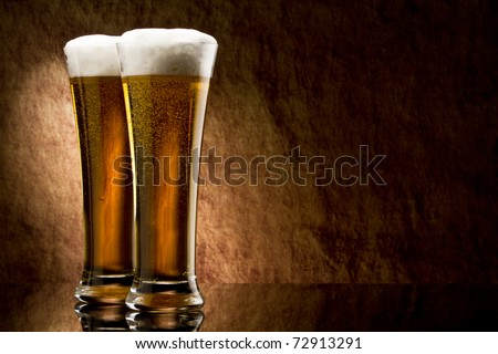 Beer into glass on a old stone - stock photo