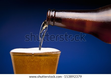 Beer is being poured in a glass. - stock photo