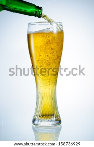 Beer is pouring from bottle  into the glass