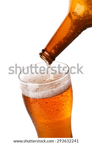 Beer is pouring into a glass over white background - stock photo