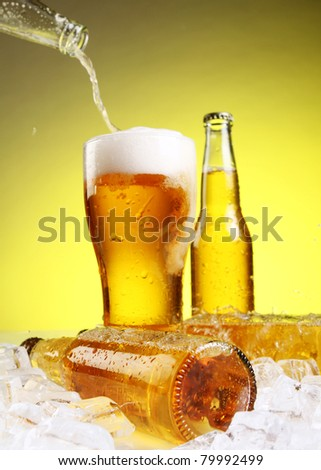 Beer is pouring into glass over yellow background - stock photo